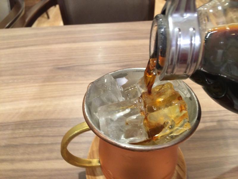 溢れんばかりに氷が入った銅製のマグカップにコーヒーを注ぎます