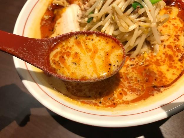 赤いまだら模様が浮かぶ白味噌風のスープ